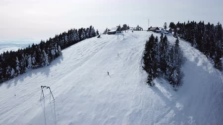 4k.Aerial. Skiers silhouettes on mountain hill. Winter time, ski lift