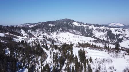4k.Aerial.Winter time in mountains, rural area.Decrease in height