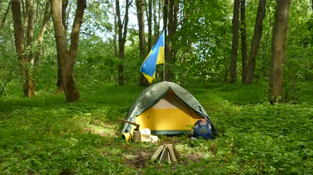 топор : 4K. Tourist camp, tent with Ukrainian flag in wood. Approach scene
