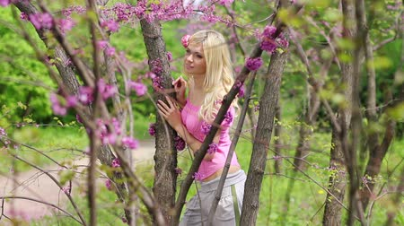 şaşırtıcı : Young beautiful girl standing in the middle of spring flowering pink trees in the park.