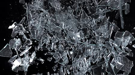 shattering : Window pane, glass falling against black background, slow motion