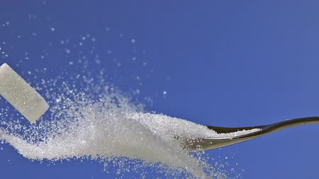 глыба : White Sugar Cube falling against Blue Background, Slow Motion