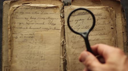 Hands searching in the vintage book with magnifying glass.