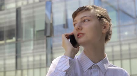 Business woman talking by phone in front of modern office buildings.
