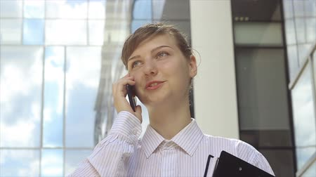 Energetic, young business woman talking by phone in front of modern office buildings.