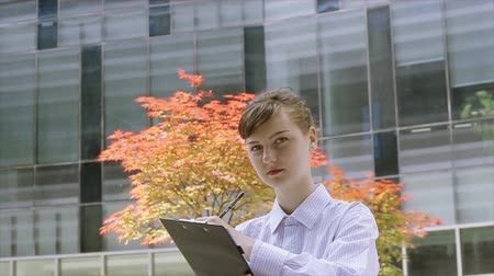 Office worker with Clipboard looking at camera in front of modern office buildings. Стоковые видеозаписи