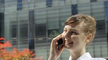 Smile and Success.  Young woman talking by phone in front of modern office buildings.