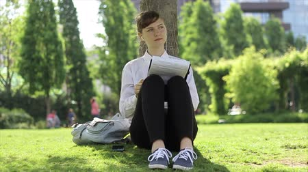 boyish : Young woman listening music while reading. Stock Footage