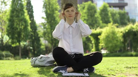 мысли : Young woman using headphones, and working in the park. Стоковые видеозаписи