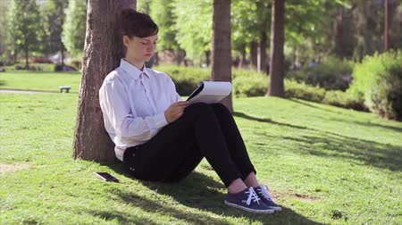 boyish : Young business womanstudent doing her tasks in the park. Stock Footage
