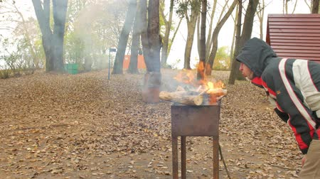 briquettes : Happy group of friends having fun at outdoor bbq barbecue in the autumn forest