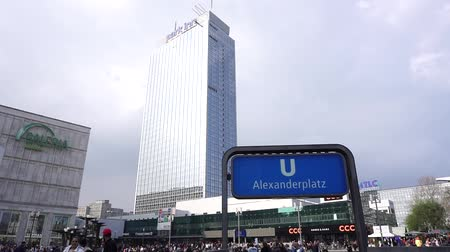 karczma : Alexanderplatz, Berlin, Germany, April 14 2018: Crowd People walking Alexanderplatz Square, Alexanderplatz Railway Station U-Bahn sign, Park Inn hotel building, clouds blue sky, cityscape background Wideo