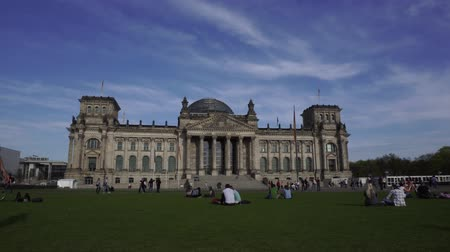 bundestag : Reichstag Building, Berlin, Germany, April 15 2018: People relaxing on grass field in front of Reichstag Building above against sky, outdoors view, 4K filmed on Sony a6300 Stock Footage