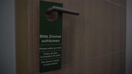 szobalány : Please Make Up Room green attention sign hang on closed hotel room door handle. Message to maid staff service to clean space, concept. German, English, French, Italian Languages.