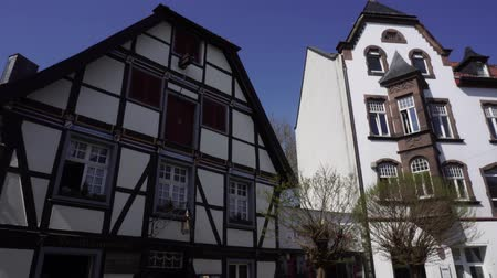 обрамление : Soest, Germany, April 18 2018: Fachwerkhaus or fachwerk is traditional german half-timbered house. Wooden frame or timber framing on exterior facade wall of building on street in city center, 4K.