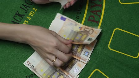 fifty : Woman dealer hands counting money. Fifty Euro bills or notes in cash on Blackjack green deck table in casino. Background concept of gambling game and entertainment in Europe, close up