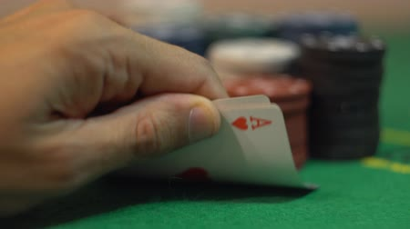 азартная игра : Gambler revealing four aces, player whirl playing cards on casino green table, concept of fortune, stacks of poker chips on background.