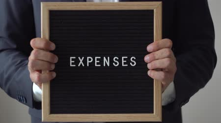 letter board : Word Expenses from letters on text board in anonymous businessman hands. Man in suit going towards to camera from blurred background, holding black wooden message board, business concept, close up, 4K