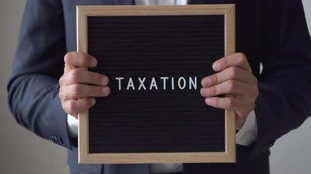 névtelen : Word Taxation from letters on text board in anonymous businessman hands. Man in suit going towards to camera from blurred background, holding black wooden message board, business concept, close up, 4K