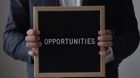 dopis : Word Opportunities from letters on text board in anonymous businessman hands. Man in suit going towards to camera from blurred background, holding black wooden message board, business concept, close up, 4K