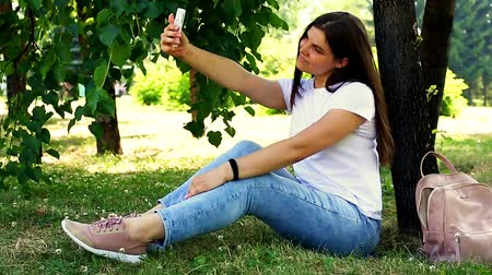 Young sitting on the grass and making selfie with a mobile phone Dostupné videozáznamy