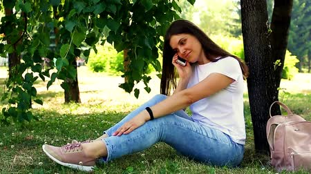Young sitting on the grass calling ans speaking on mobile phone
