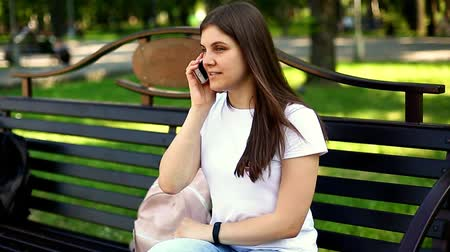 Young sitting on the bench calling ans speaking on mobile phone Dostupné videozáznamy