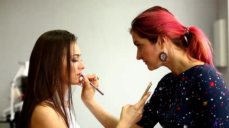 щетка для волос : Make-up model and make-up artist working in studio.