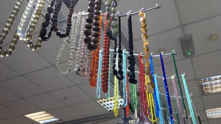 colar : Different colorful stone necklaces on a hanger