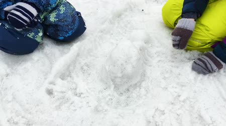sněhulák : Kids playing with melting snow, making shapes of snow