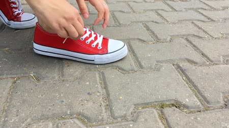 red tie : Woman tiying shoelaces on red sneakers. Womans feet in red sneakers shoes on the road in city