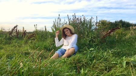 わら : Happy beautiful brunette teenage girl sitting on the grass, smiling and touching her hair