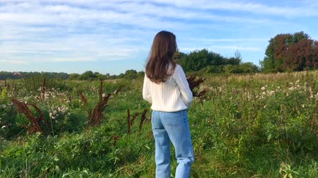 Happy beautiful brunette teenage girl walking in a green field with a bouquete of dry brown plants