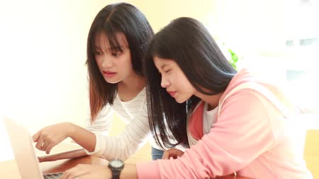 acadêmico : Asian University or college students studying together with tablet,laptop and documents paper for report near windows in classroom. Happy Asian young woman doing group study in Education class Concept