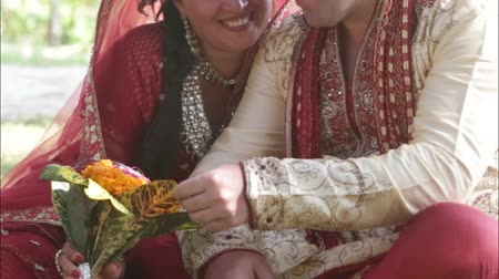 asian and indian ethnicities : Indian bride and groom stroking bouquet smile