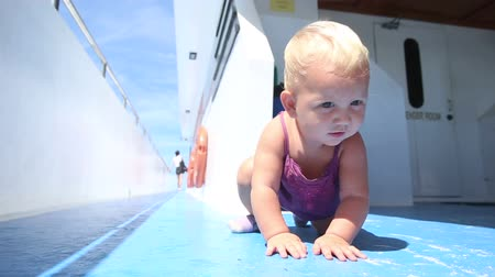 convés : blond child sitting on a blue ship deck and looking at the camera