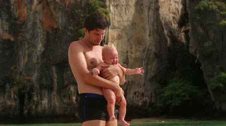 baby blue : brunette man holding a crying baby on a background of the tropical rocky island