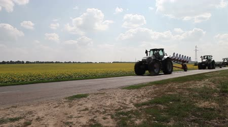 arado : three tractor with plow and drill driving on asphalt road on the background field of sunflowers and clouds