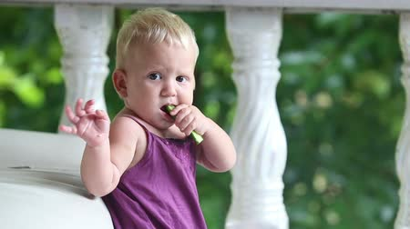 zeleninový : child eating cucumber standing leaning on the sofa against the background of columns and greenery Dostupné videozáznamy