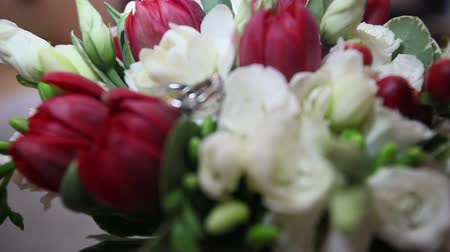годовщина : on the bouquet of red and white roses lays wedding rings