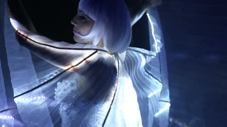 dancer : beautiful actress girl in white clothes and unusual white wigs dancing with LED wings that glow on the stage under the floodlights at night
