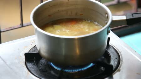 soup pans : chicken with noodles and potatoes cold soup in a small saucepan on the gas stove near the window lit the gas