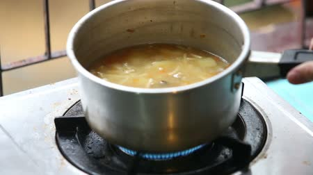 soup pans : chicken soup in a small saucepan put on the stove ignited gas boils Stock Footage
