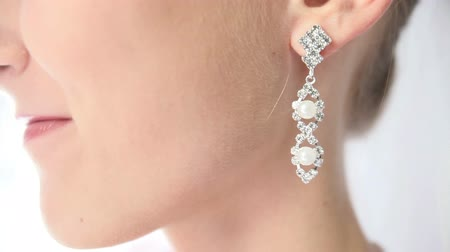 дорогой : earring with pearls in silver framehanging on the ear of the bride