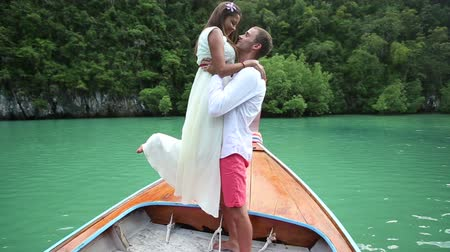брюнет : brunette bride kiss her handsome groom on longtail boat in Hong island lagoon in Thailand Стоковые видеозаписи