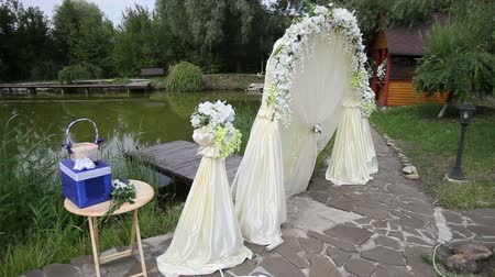 cerimônia : white arch for wedding on the lake near the trees and stone paths and wooden houses