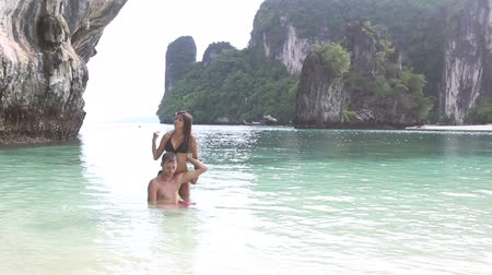 romantic : brunette girl with handsome man swim in island bay with green mountain background in Thailand