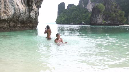 медовый месяц : brunette girl with handsome man swim in island bay with green mountain background in Thailand