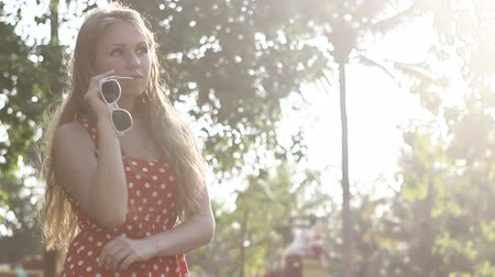 giydirmek : blonde girl in a red polka-dot dress puts his hand on her hip on the background of palm trees on the backlit Stok Video