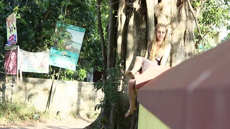 banyan : VARKALA, KERALAINDIA - JANUARY 01 2013: girl sitting on a fence near the banyan tree and the road with motorcycles Pass and billboards on January 1 in Varkala Stock Footage